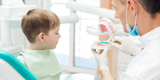 Dentist in Chester-le-Street educating little boy about brushing teeth demonstrating on dental jaw model in clinic